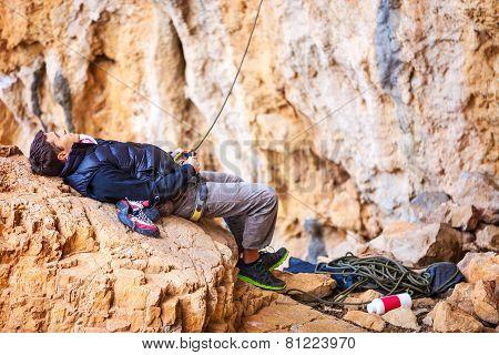 Man watching leading rock climber while belaying