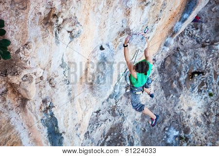 Climber holding on handhold while climbing cliff