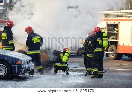 Warsaw, Poland - January 27, 2015: Firefighters are extinguishing a car on fire at main road in Warsaw.
