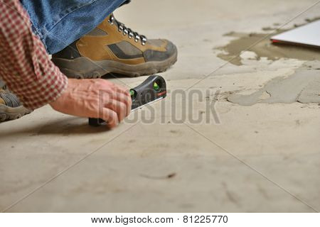 Worker checking the surface using spirit level during the tiled floor installation