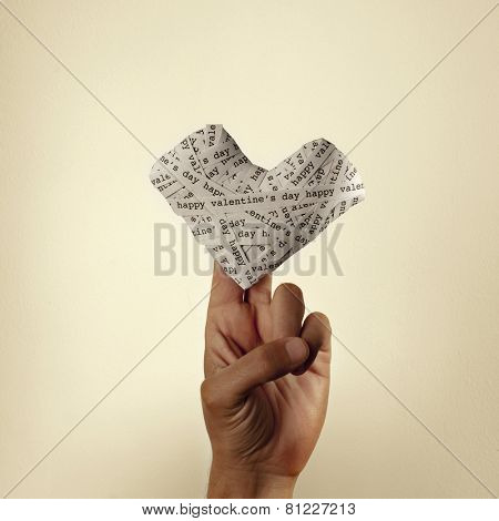 the hand of a young man holding a heart made-up with paper strips with the text happy valentines day, with a retro effect
