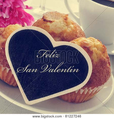 the text feliz san valentin, happy valentines day in spanish, written in a heart-shaped signboard, in a plate with magdalenas, spanish plain muffins