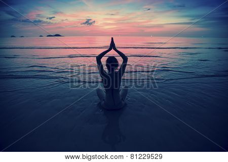 Silhouette young woman practicing yoga on the beach at surrealistic sunset. Yoga and fitness.