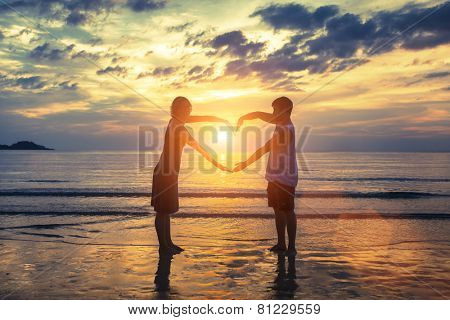 Silhouette of young romantic couple during tropical vacation, holding hands in heart shape on the ocean beach during sunset. Love story. Romantic wedding couple.
