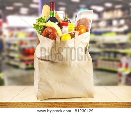 Brown table and on background blured supermarket and bag with products