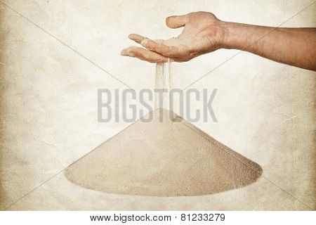 sand running through hand as a symbol for time running out. Cracked paper background