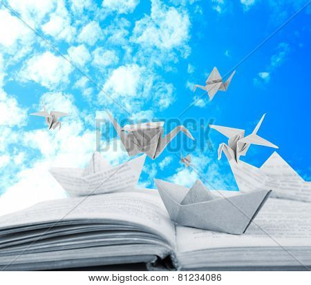 Origami boats and cranes on book on sky background