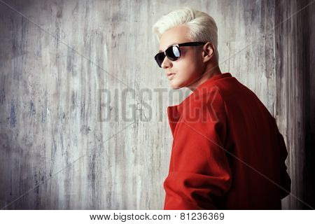 Close-up portrait of a fashionable male model with blond hair wearing red coat and black sunglasses. Men's beauty, fashion.