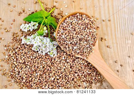 Buckwheat on board with flower and wooden spoon
