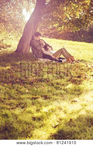 Love couple sitting under a tree in the colorful autumn forest