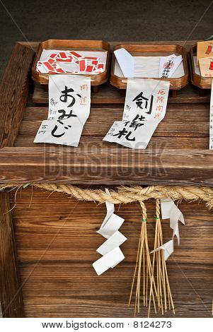 A Table Displaying Items For Sale (prayer Notes And Fortunes) At A Japanese Temple