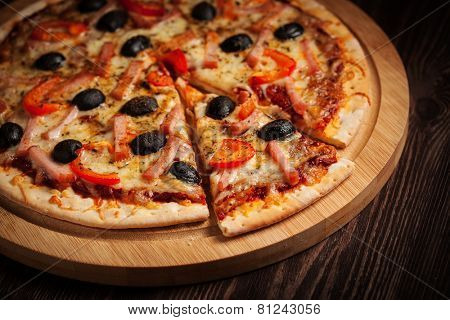 Sliced ham pizza with capsicum and olives on wooden board on table