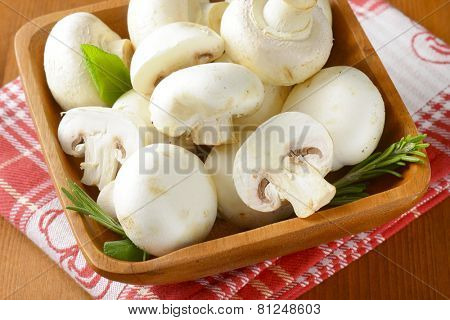 wooden bowl full of white unpeeled mushrooms