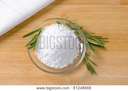 glass bowl with coarse grained salt with sprig of rosemary
