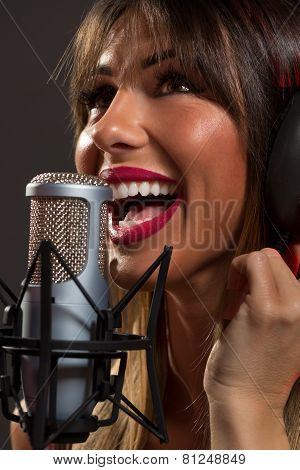 Happy Woman Singer In Front Of The Microphone