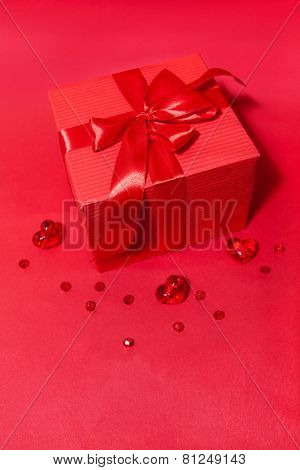 Gift box with bow and hearts on the red background