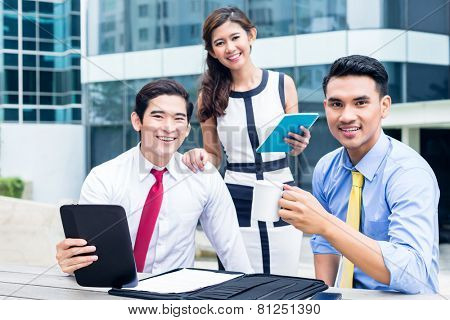 Asian business woman and men working outside on computer drinking coffee