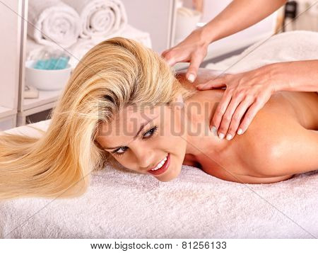 Blond woman getting massage in health resort. Lying on terrycloth