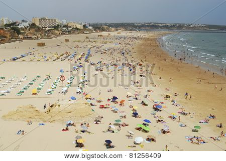 People sunbathe at Praia da Rocha beach in Portimao, Portugal.