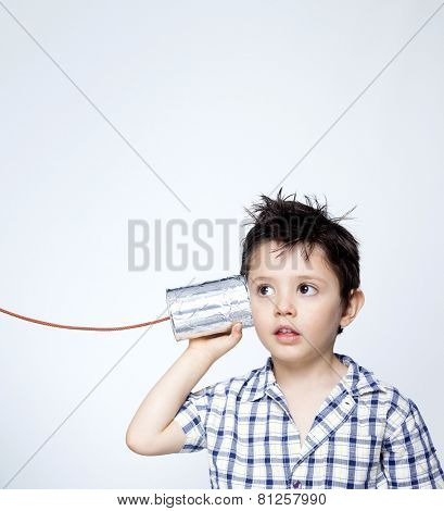 Child using a can as telephone against gray background
