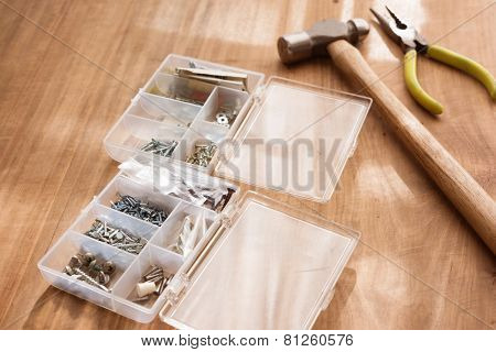 Screw and nail tray or compartment box, and a hammer by a warm window light.