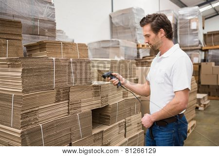 Serious warehouse worker holding scanner in warehouse
