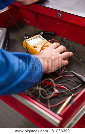Mechanic taking a diagnostic tool from drawers at the repair garage