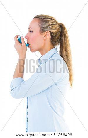 Beautiful blonde using an asthma inhaler on white bakcground