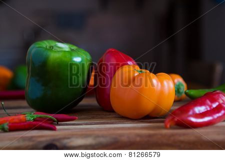 Assortment of peppers on a chopping block on a table in a kitchen