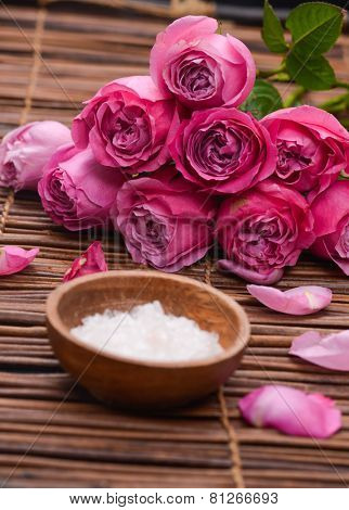 Rose petals with salt in wooden bowl on mats