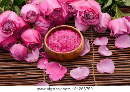 Rose with rose petals, salt in wooden bowl on mat