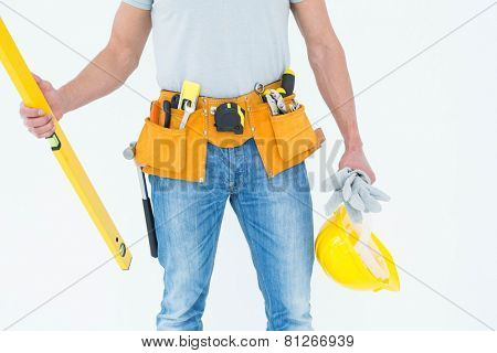 Repairman holding spirit level and hardhat over white background