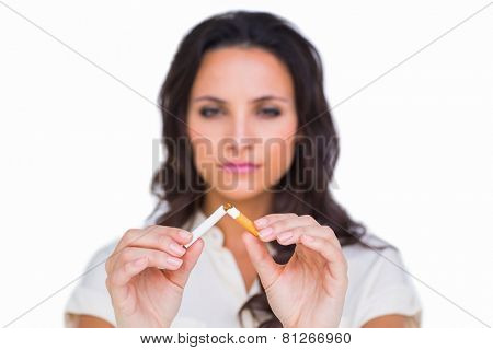 Pretty brunette breaking a cigarette on white background