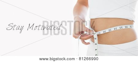 Closeup midsection of woman measuring waist over white background