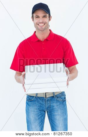 Portrait of happy delivery man holding pizza boxes on white background