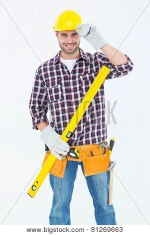 Portrait of confident handyman holding spirit level on white background