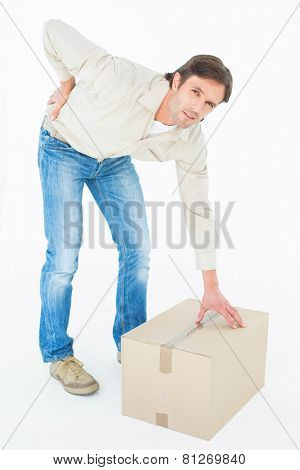Full length portrait of delivery man with cardboard box suffering from back ache on white background