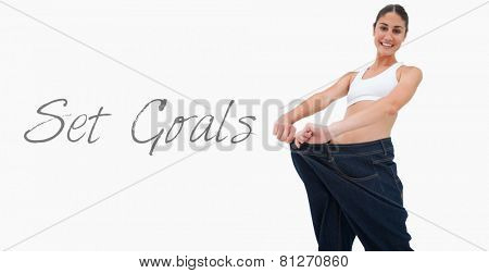 Brunette in a jeans too big against white background