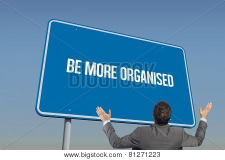 The word be more organised and businessman posing with arms raised against blue sky