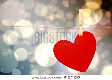 Heart hanging on line against light glowing dots design pattern