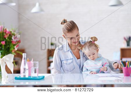 Young mother and her little daughter drawing with crayons