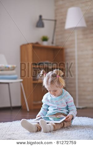 Little girl with touchpad spending leisure at home