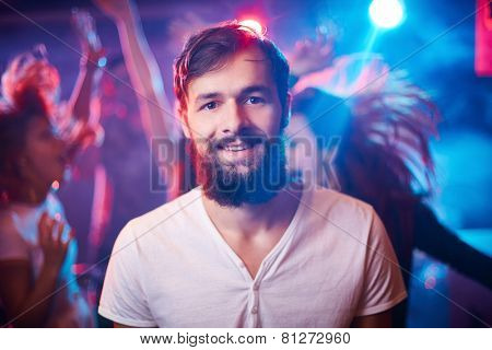Bearded guy looking at camera while ecstatic friends dancing on background