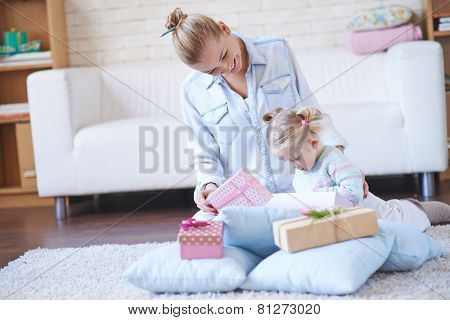 Happy woman showing her little daughter giftboxes with presents