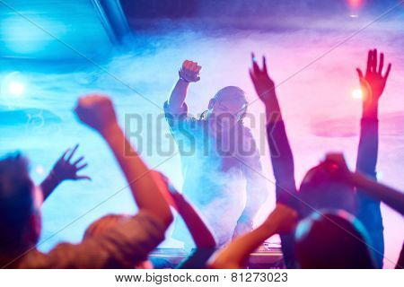 Excited deejay encouraging dancing crowd in nightclub