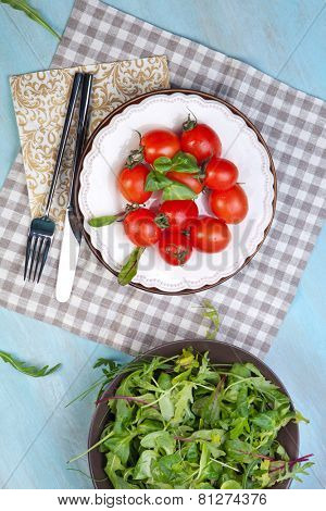 Fresh red delicious tomatoes in plate on an wooden table
