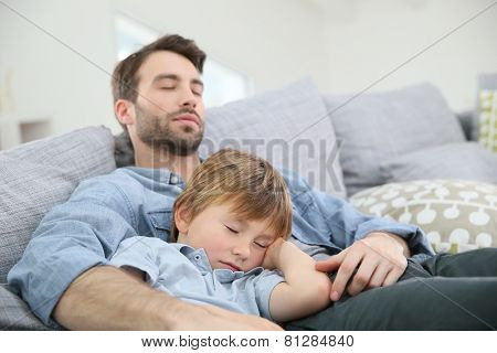 Father and son taking a nap on sofa