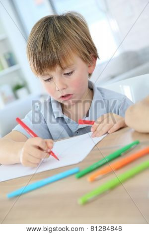 Portrait of smiling 6-year-old boy making drawing
