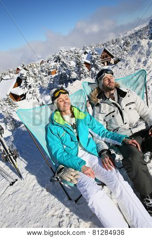 Couple of skiers sunbathing in long chairs