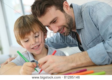 Daddy with little boy making drawings at home